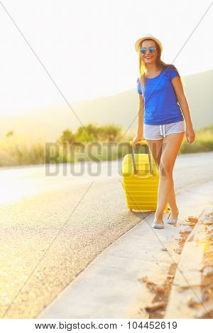 Attractive Young Woman With A Yellow Suitcase Is Traveling On The Road Hitchhiking