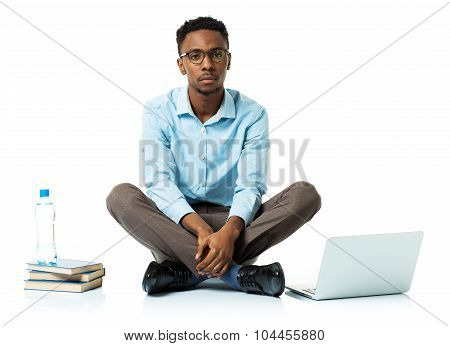 Serious African American College Student With Laptop, Books And Bottle Of Water Sitting On White