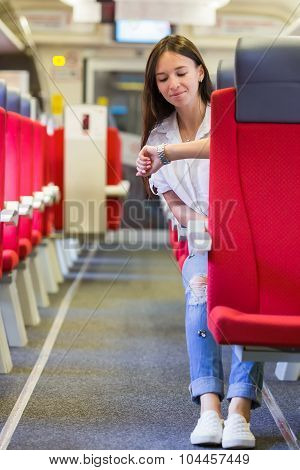 Young happy woman traveling by train