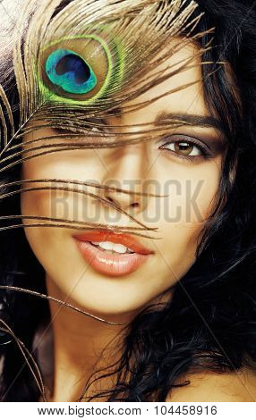 young sensitive brunette woman with peacock feather eyes close up on green