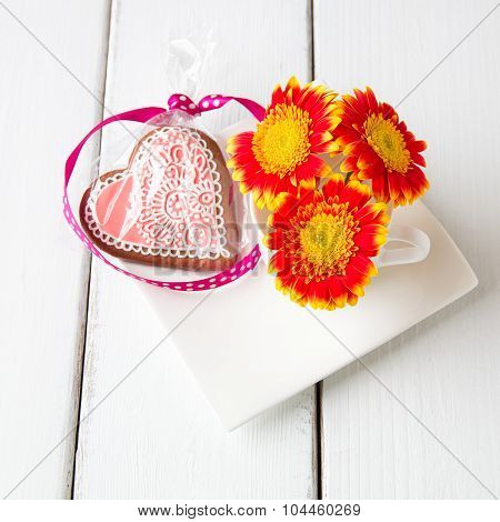 Cup Full Of Pink Gerbera  Flowers And  Heart Shape Cookie On White Wooden Table.