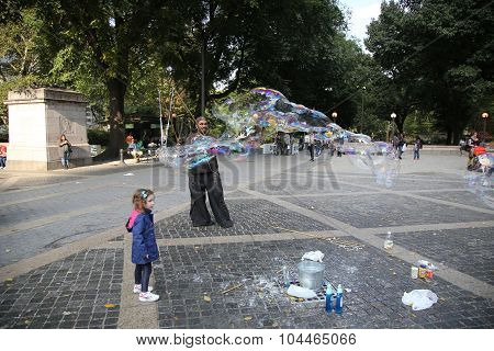 Street performer creating oversize bubbles for kids at Central Park in New York