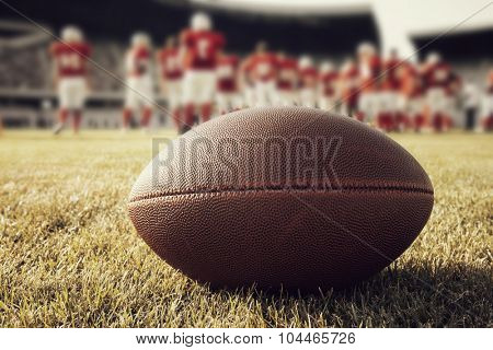 Close up of an american football on the field, players in the background - retro styled photo
