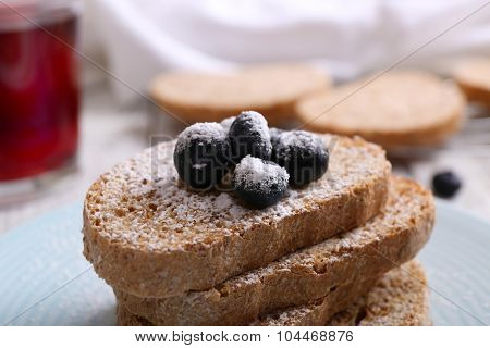 Fresh toast with berries and glass of juice on table close up