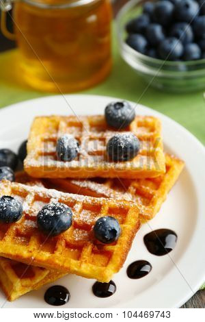 Sweet homemade waffles with forest berries and chocolate sauce on table background