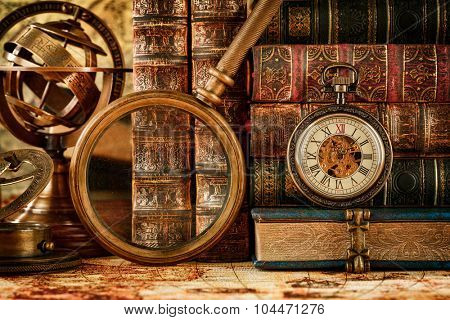 Vintage still life. Vintage magnifying glass lies, pocket watch, old book and astrolabe on an ancient world map in 1565.