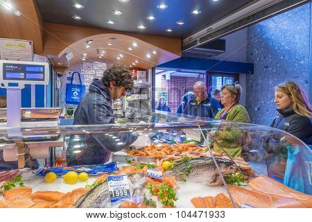 Shop assistant serving customers in a seafood shop in Melbourne