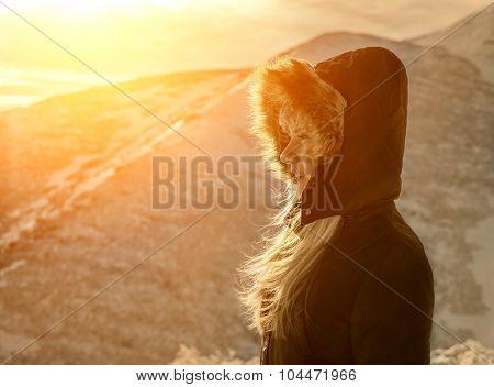 Woman stay under sun light. Beautiful winter mountains view.