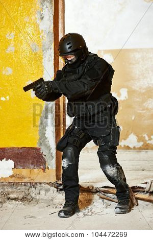 Military industry. Special forces or anti-terrorist police soldier,  private military contractor armed with pistol ready to attack during clean-up operation, mission