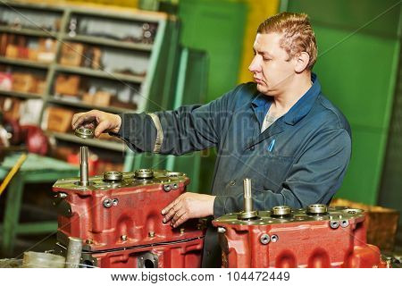 industrial worker assembler with gearbox utits at manufacture workshop