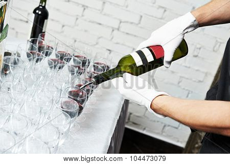 Waiter bartender pouring red wine into glasses at party event