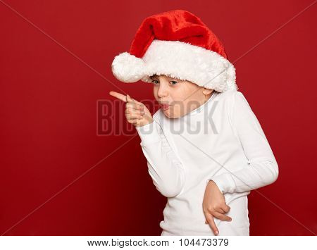 winter, child,  christmas concept - happy girl in santa hat dancing on red background