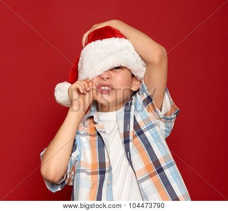 winter holiday christmas concept - boy in santa hat close one eye on red background