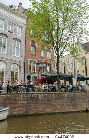 People Near Cafe On The Waterfront Of Canal In Amsterdam