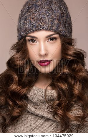 Beautiful girl with gentle makeup, curls in brown knit hat. Warm winter image. Beauty face.