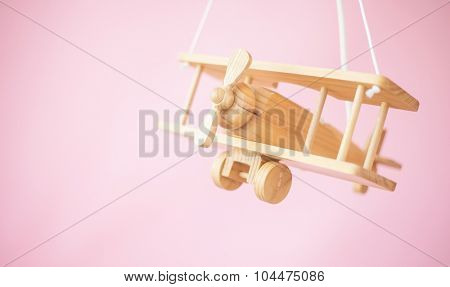 Wooden airplane on pink background