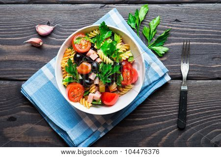 Salad with pasta, ham and vegetables in white bowl on wooden rustic background