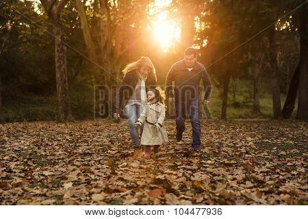 Outdoor portrait of a happy family enjoying the fall season