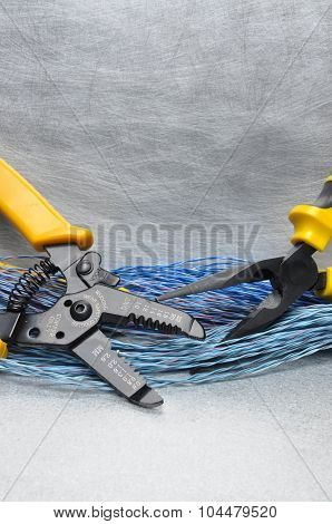 Crimping tool pliers and cables on grey background