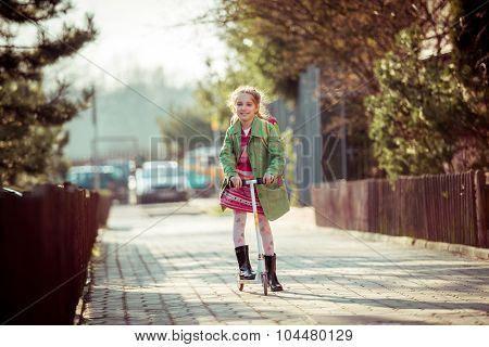 girl returning from school on a scooter