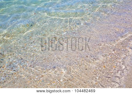 Background with pebbles and sand under water at the coast of Mediterranean sea