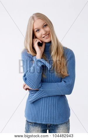 Happy young blonde woman looking away, touching face.