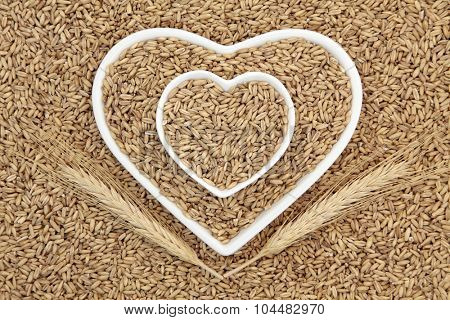 Oat groat health food cereal grain in heart shaped bowls with wheat sheaths forming an abstract background.
