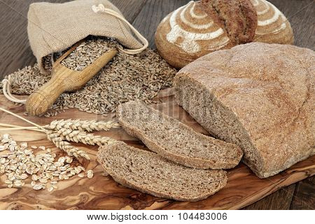 Organic brown bread loaves on an olive wood board with rye flakes and grain in a hessian bag over oak background.