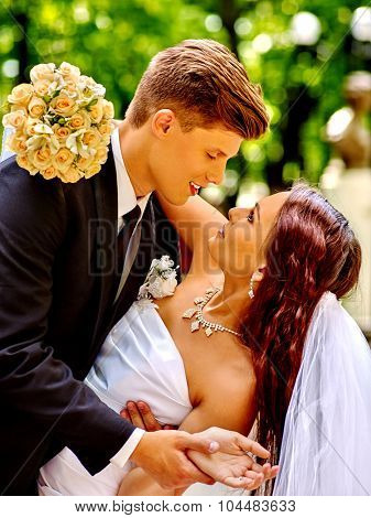 Bride and groom with flower summer  kissing outdoor.