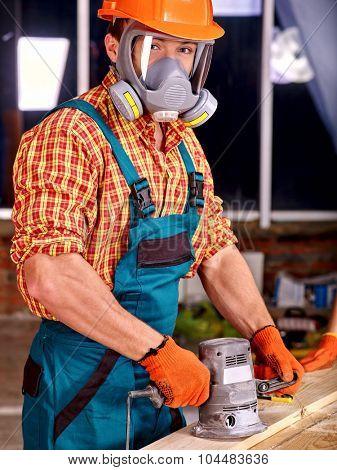 Man worker in builder helmet with electric planer. Indoor.