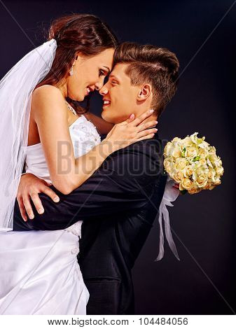 Bride and groom wearing wedding dress and costume happy kissing.