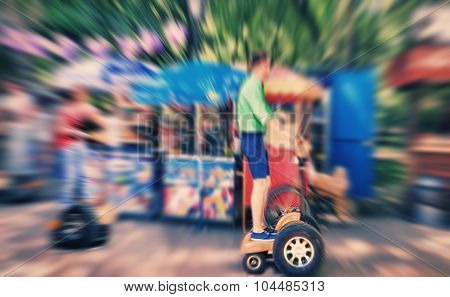 Abstract Background. A Young Man Riding A Segway In The Park.  Blur Effect Defocusing Filter Applied