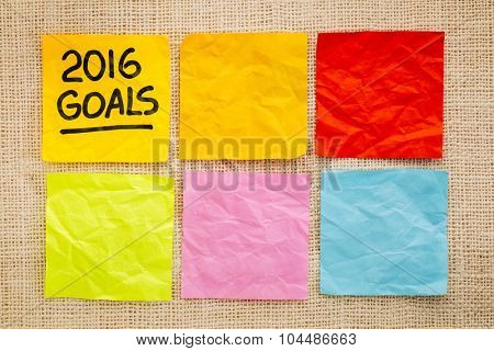 2016 New Year goals - handwriting on a sticky note against grained wood with blank notes