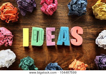 Design thought process with the word ideas and crumpled paper balls