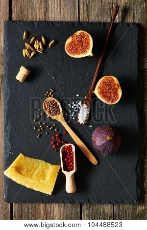 Spices, cheese and figs over slate