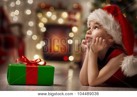 Funny smiling child in Santa red hat