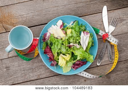 Plate with fresh salad, measure tape, cup, knife and fork. Diet food on wooden table