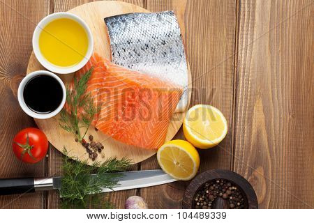 Salmon, spices and condiments on wooden table. Top view with copy space
