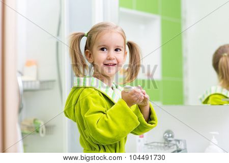 Cute little girl washing hands in bathroom