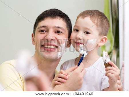 cute little boy and father shave looking at mirror in bathroom