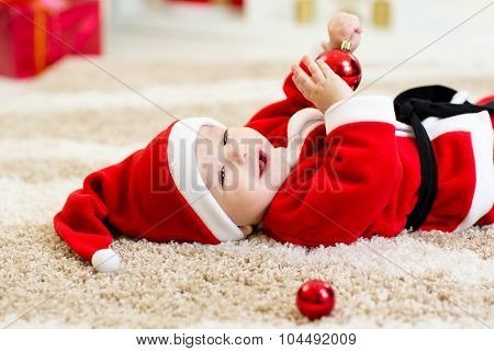 Baby boy weared Santa hollding christmas ball