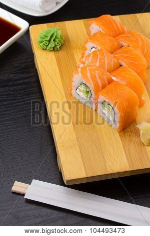 Sushi Roll With Salmon With Chopsticks Over Dark Wooden Background