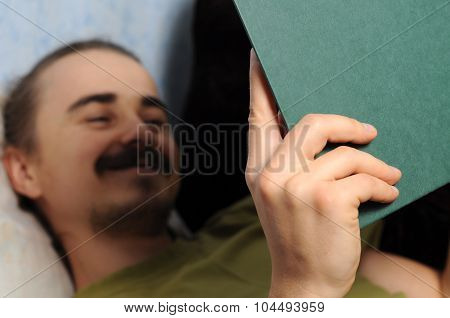 Happy Man Reading Book Lying On Coach