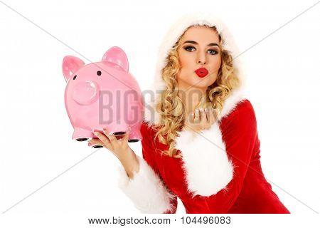 Santa woman holding a piggy bank and sending a kiss.