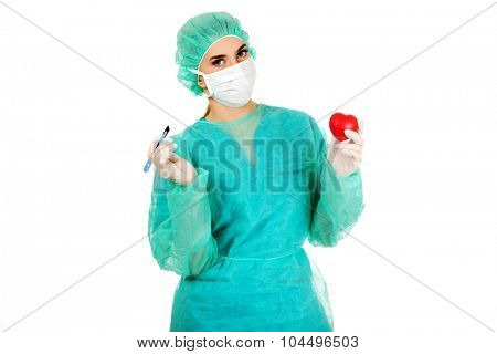 Young female cardiologist surgeron holding heart and scalpel.