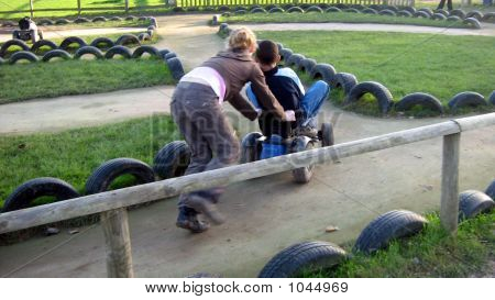 Teenager/Girl Playing/Pushing Boy On A Toy Tractor.Leisure.Children Playing