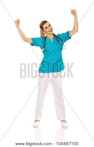 Young happy female doctor with hands up. Winning concept