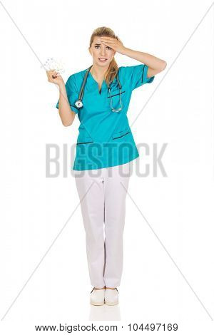 Shocked female nurse or doctor holding pills.