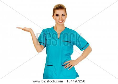 Smiling woman doctor or nurse pointing something.