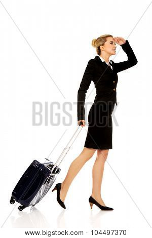 Businesswoman with wheeled suitcase covering eyes with hand.